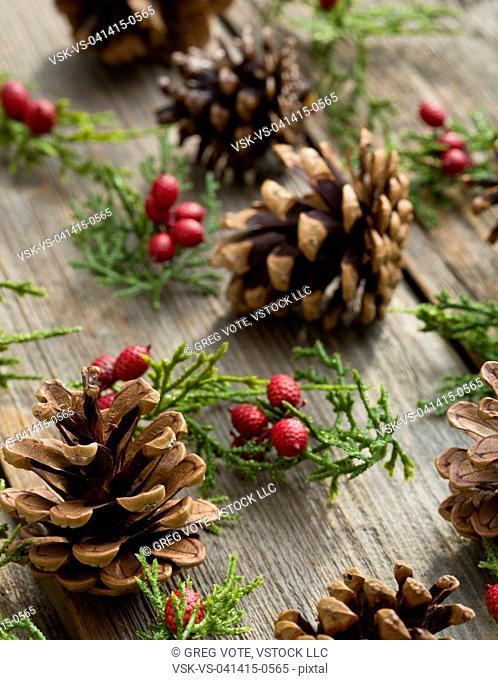 Pine cones and elderberries on wooden plank