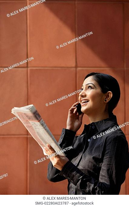 woman talking on phone, holding newspaper