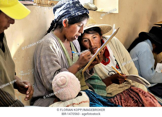 Women in traditional dress of the Quechua signing up for a course in the attendance list, Bolivian Altiplano highlands, Departamento Oruro, Bolivia