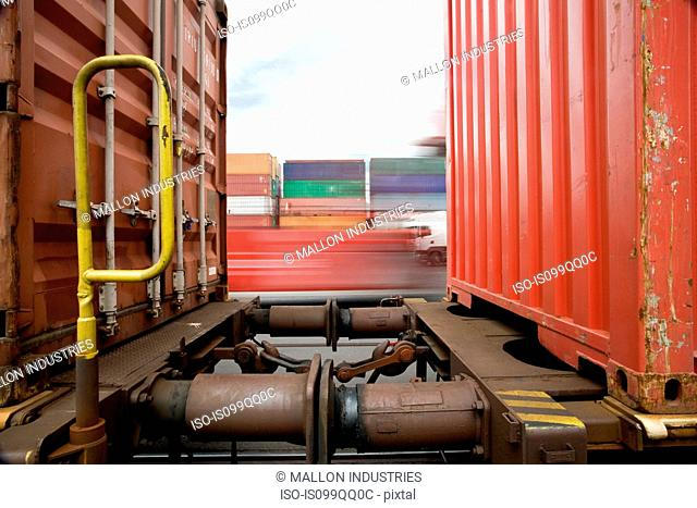 Train passing shipping containers