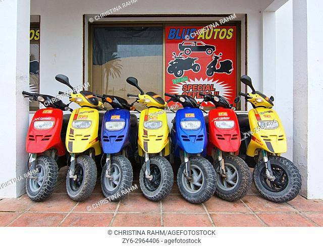 Seven scooters in blue, yellow and red colors packed together in Formentera, Balearic islands, Spain
