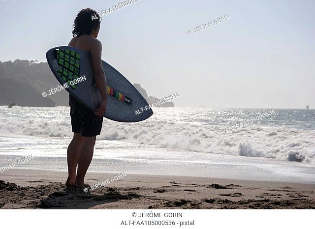 Surfer standing at water's edge, looking at sea