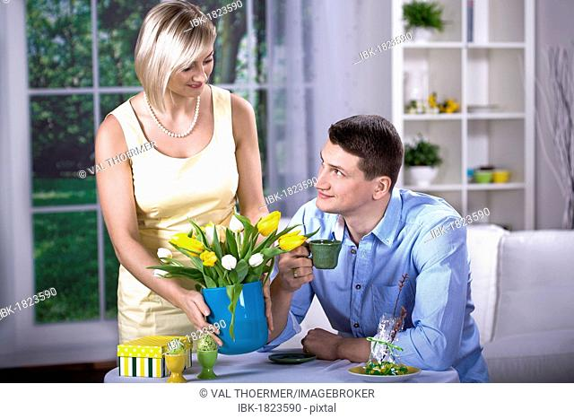 Young couple at a table with tulips in a vase and Easter eggs