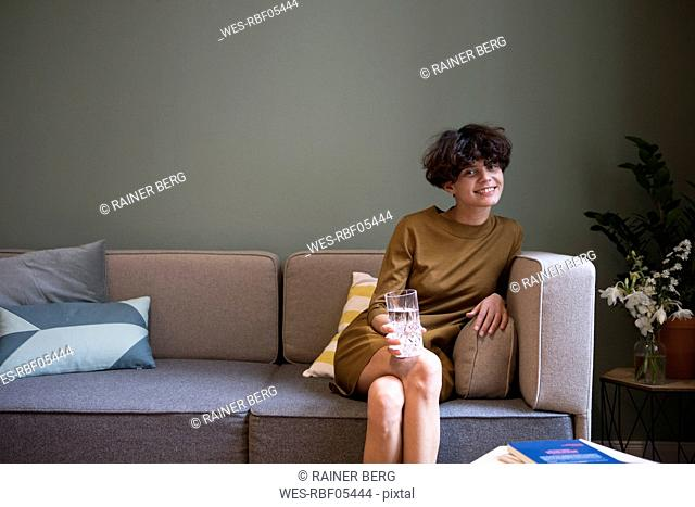 Portrait of smiling young woman with glass of water sitting on couch at home