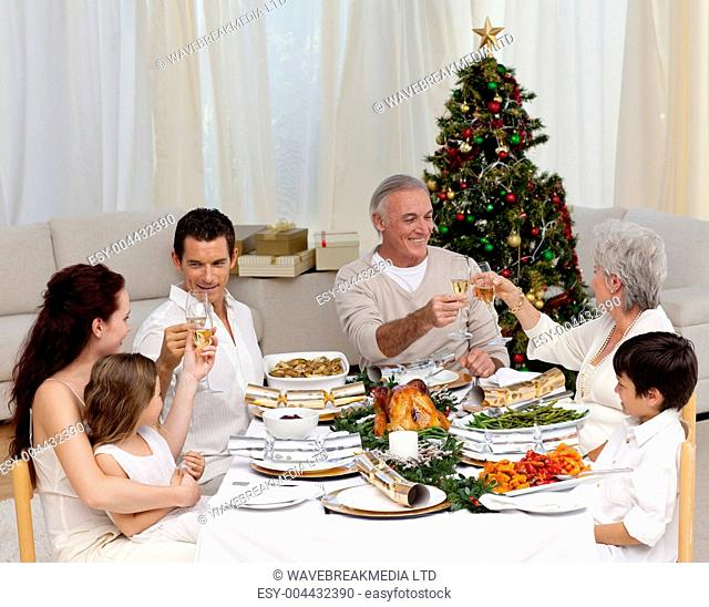 Grandparents and parents tusting in a Christmas dinner