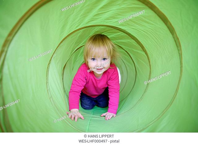 Portrait of smiling little girl crawling in a bright green tunnel