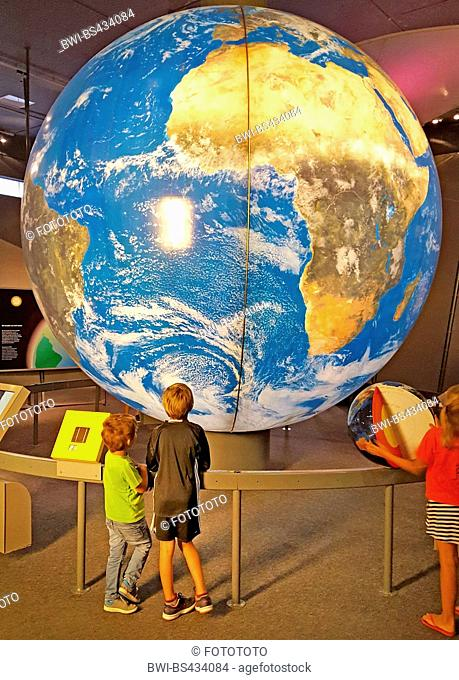 two children looking at a big globe