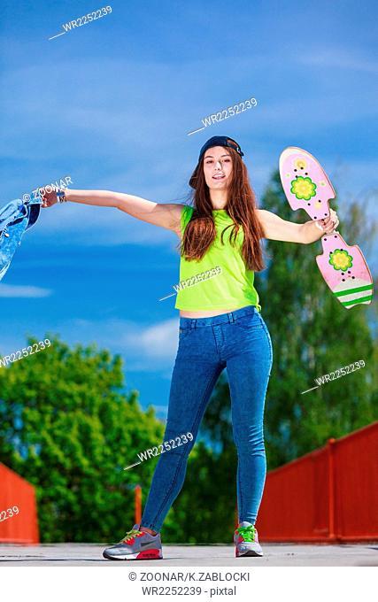 Teenage girl skater riding skateboard on street