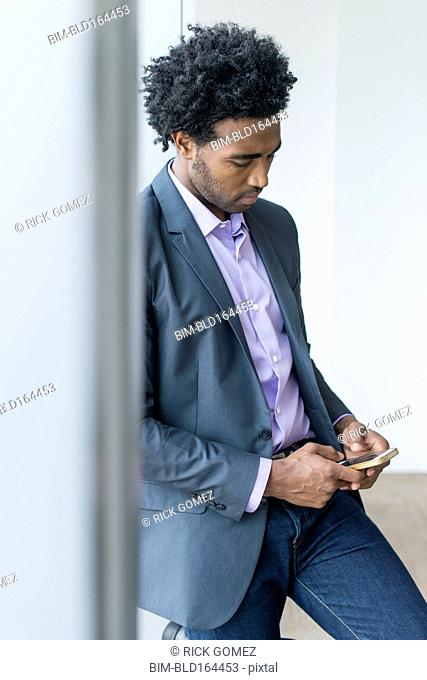 Hispanic businessman using cell phone in office
