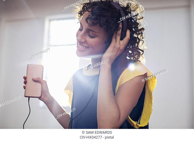 Smiling, carefree young woman listening to music with headphones and mp3 player