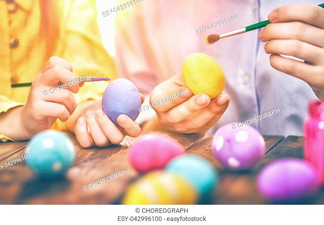Happy holiday! A mother and her child are painting eggs. Family preparing for Easter. Close up