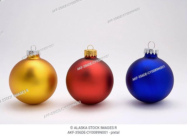 Three Christmas tree bulb ornaments on white background studio portrait