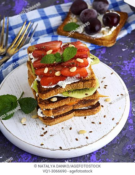 pile of French toast with cottage cheese, strawberries, kiwi and blueberries on a round white wooden board, top view