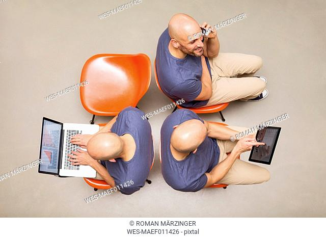 Man sitting on chairs using portable devices, multitasking