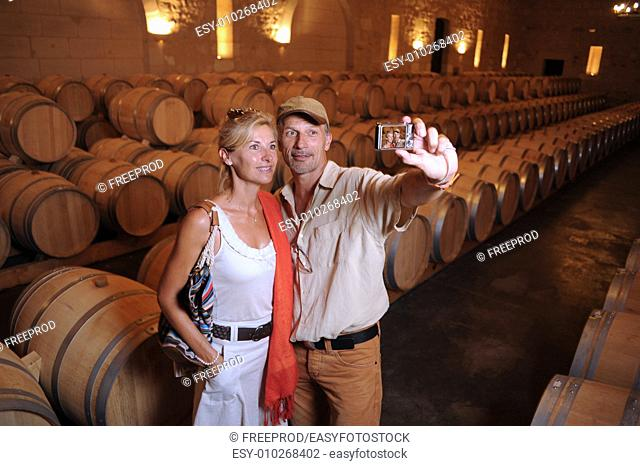 Tourism-Couple visiting a castle photographing in a barrel cellar in Bordeaux vineyard