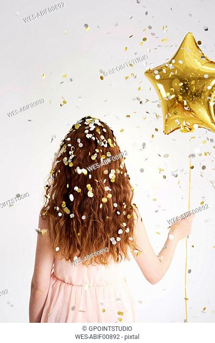 Back view of redheaded young woman with star-shaped golden balloon under shower of confetti