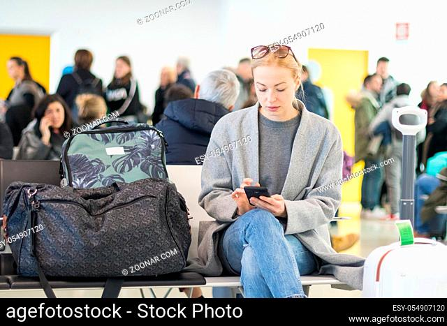 Casual blond young woman reading on her mobile phone while waiting to board a plane at the departure gates at the airport terminal. Travel concept