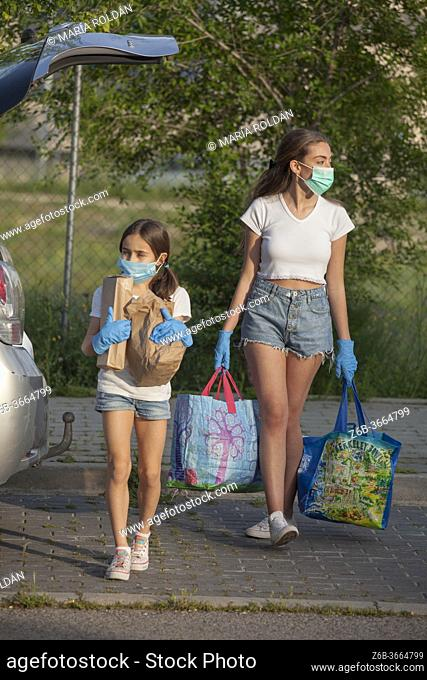 people wearing mask and gloves coming home from supermarket