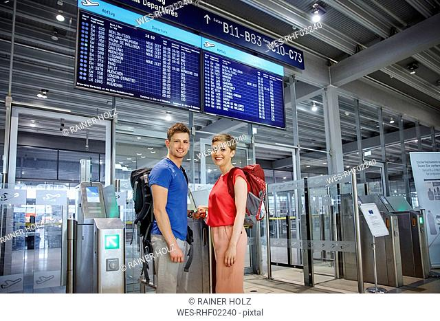 Portrait of smiling couple at security gate at the airport