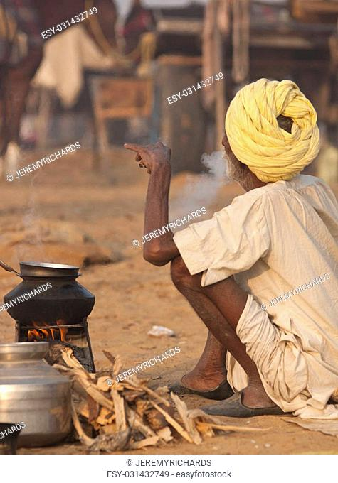 Old man smoking next to his camp fire at the annual Pushkar Camel Fair in Rajasthan, India