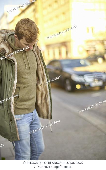 Young man walking at street in city, wearing jacket, in Munich, Germany