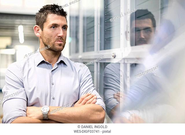 Businessman at glass pane in modern factory thinking