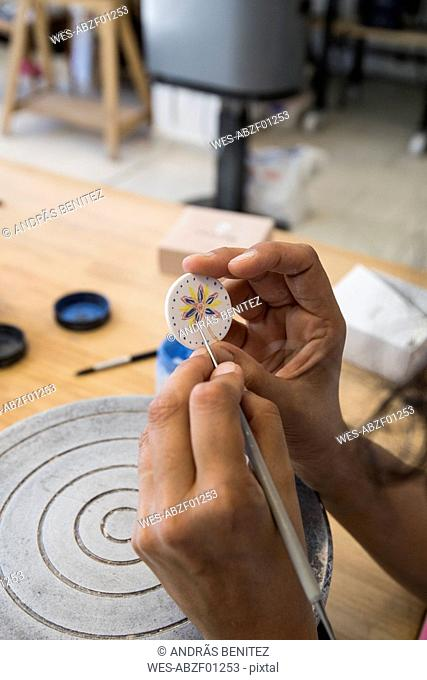 Woman painting a ceramic pendant with a brush