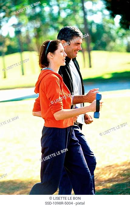 Side profile of a mid adult couple jogging together