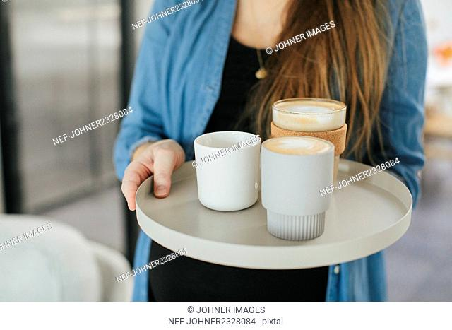 Woman with coffees on tray