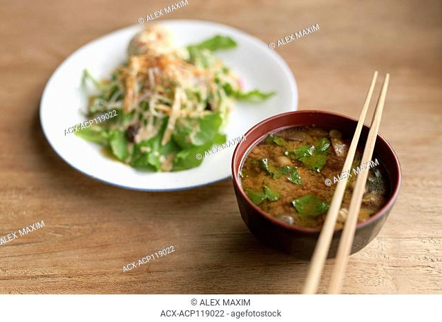 A bowl of spicy Miso soup and a plate of vegetable salad in a Japanese vegan restaurant, food still life on a wooden table. Kyoto, Japan