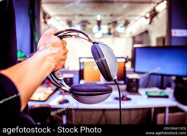 Young man holds headphones in the recording studio. Buttons, studio, screens and equipment in the blurry background