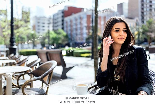 Young woman with smartphone having coffee