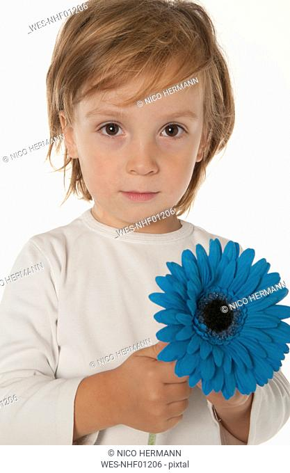 Boy 4-5 holding blue flower, portrait, close-up