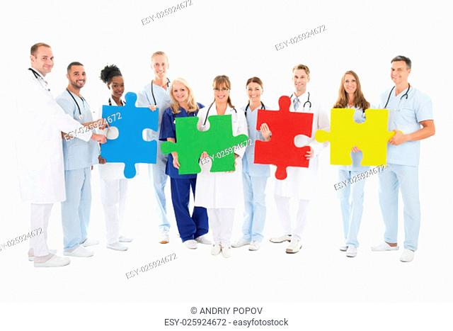 Full length portrait of confident medical team holding jigsaw pieces against white background
