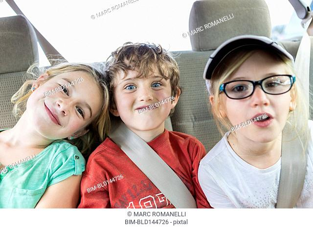 Caucasian children smiling in back seat of car