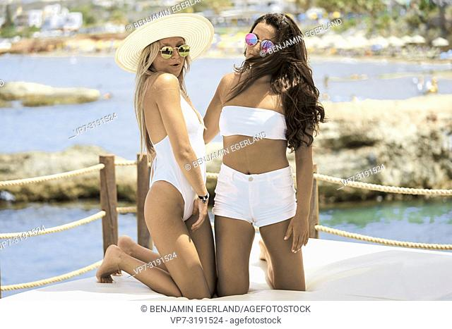Two attractive women in white bikini relaxing at luxury sunbeds next to sea. In holiday location Chersonissos, Crete, Greece