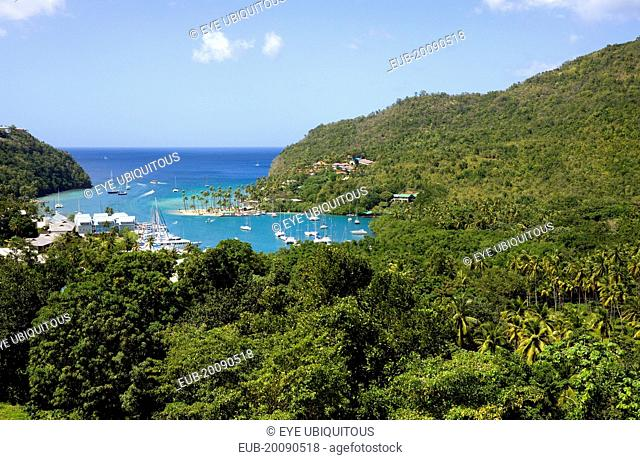 Marigot Bay with boats at anchor in the harbour below lush hillside vegetation
