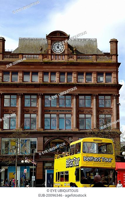 Castle Street Bank Buildings, former bank of the 4 Johns, now a retail clothing store. Yellow open top tour bus in foreground