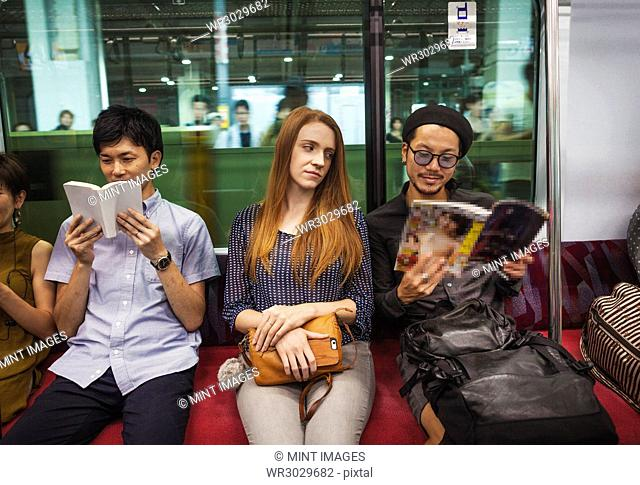 Three people sitting sidy by side on a subway train, reading,Tokyo commuters