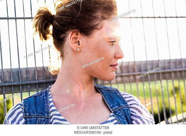 Young woman at fence in backlight