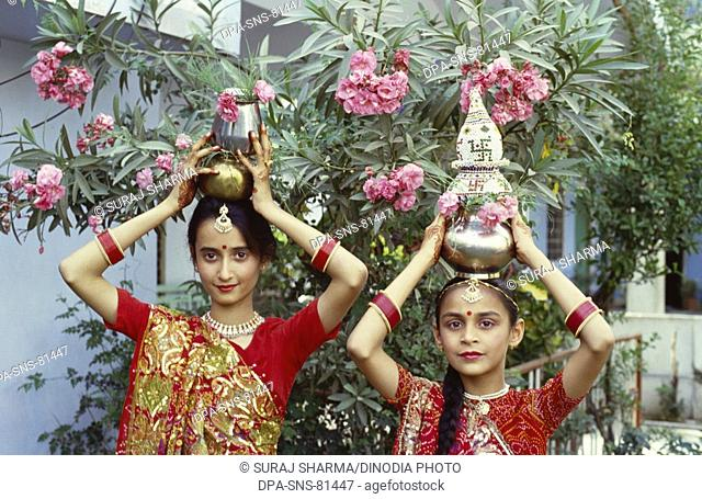 girls holding kalash on head , Gangaur festival , udaipur , rajasthan , india
