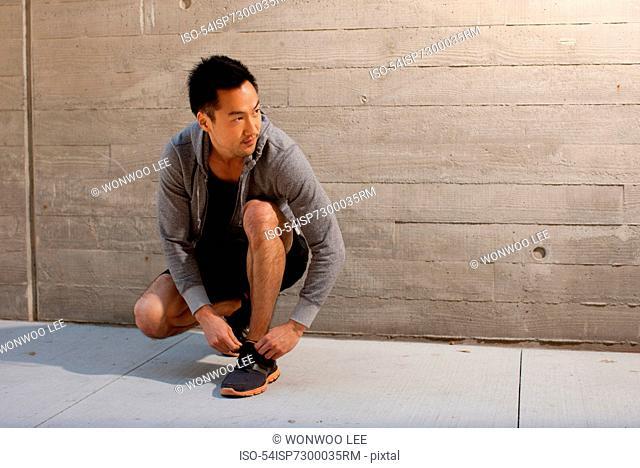 Runner tying shoes on city street