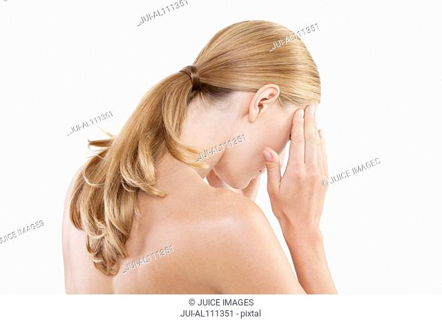 Mid adult woman touching temples against white background