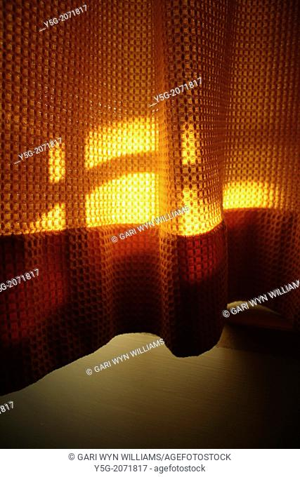 sunlight on orange curtains in room