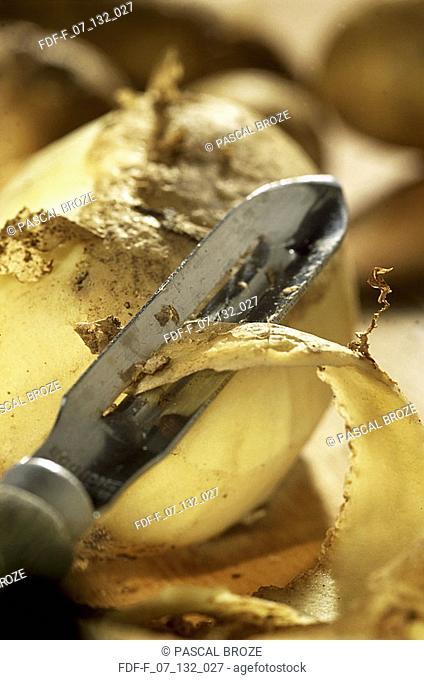 Close-up of a peeler peeling a raw potato