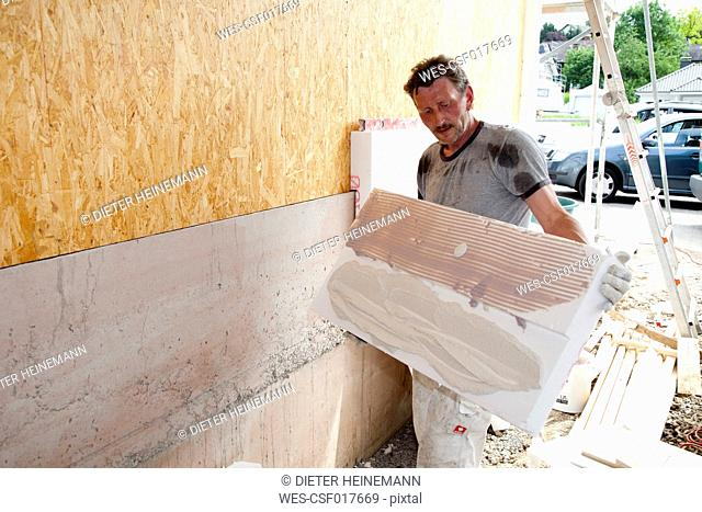 Europe, Germany, Rhineland Palatinate, Man sticking polystyrene on wooden house wall