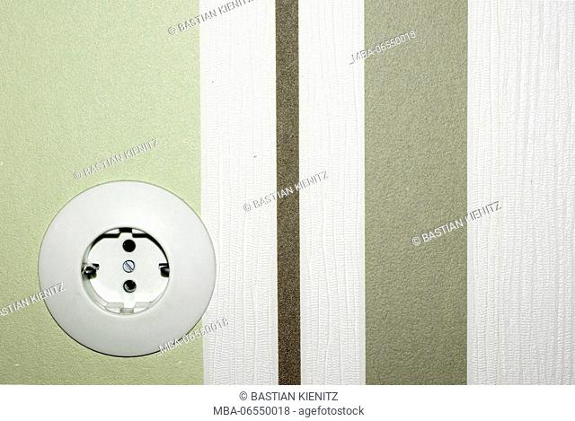 The front view of an old socket in front of a strikingly striped wallpaper