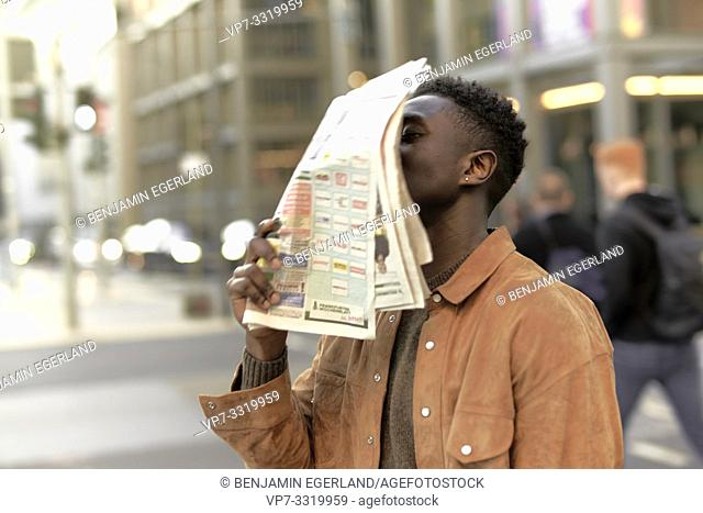 African man with newspaper at street in city, in Frankfurt, Germany