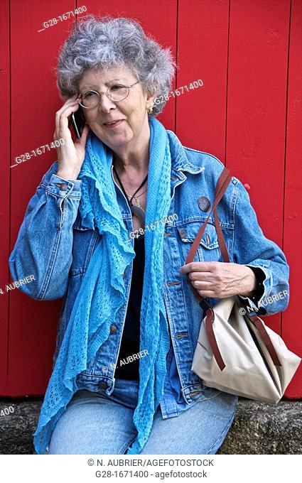Senior woman in jeans and blue jeans jacket with woolen scarf, sitting and phoning with a smile