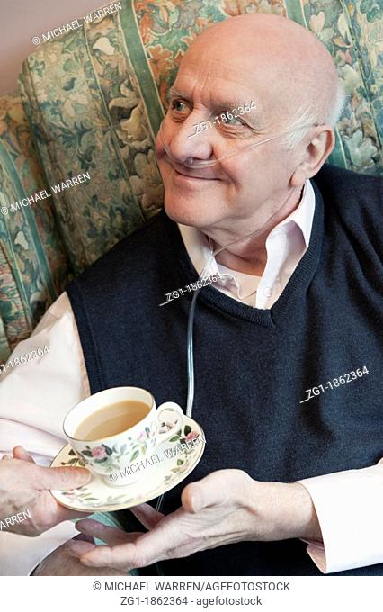 Elderly man with a carer or nurse offering a nice cup of tea